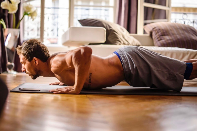 A topless man doing a push up in the living room