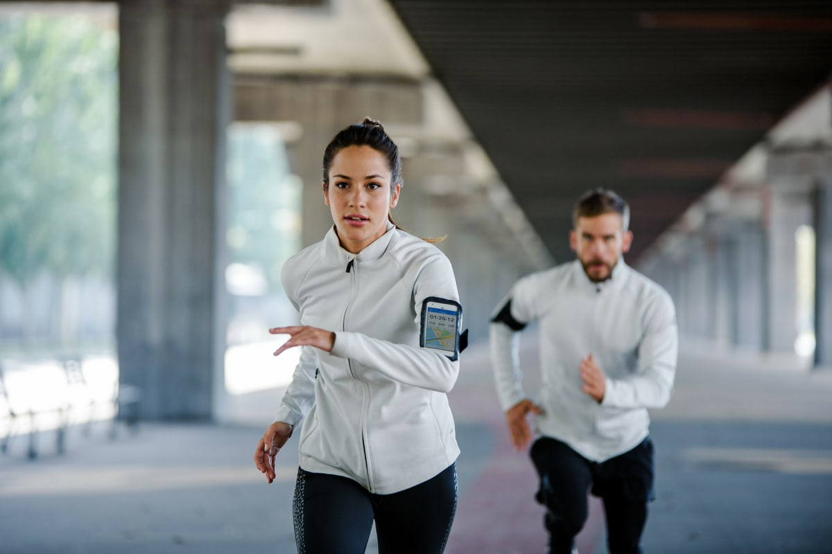 A woman and a man running intervals outside