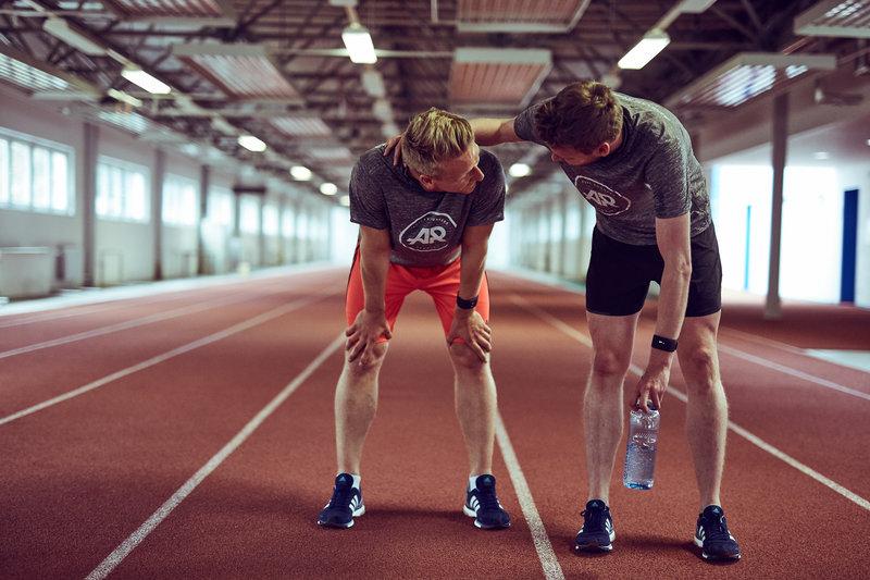 Homens cansados após correr em pista sintética.