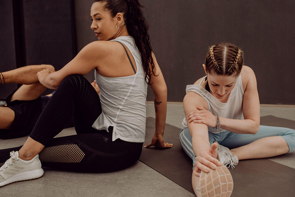 Two young women doing a workout and stretching