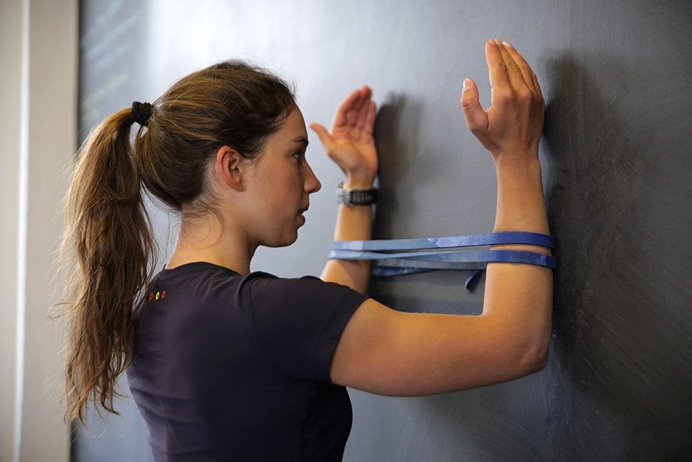 Mulher fazendo exercício para os ombros com faixa elástica