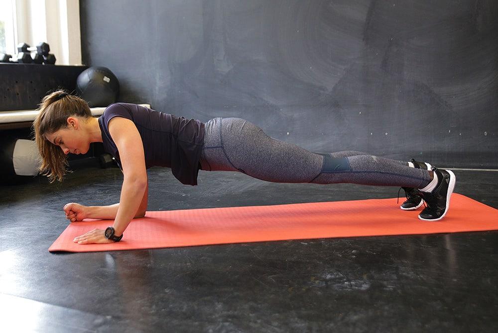 Mulher fazendo prancha dinâmica para estabilidade dos ombros
