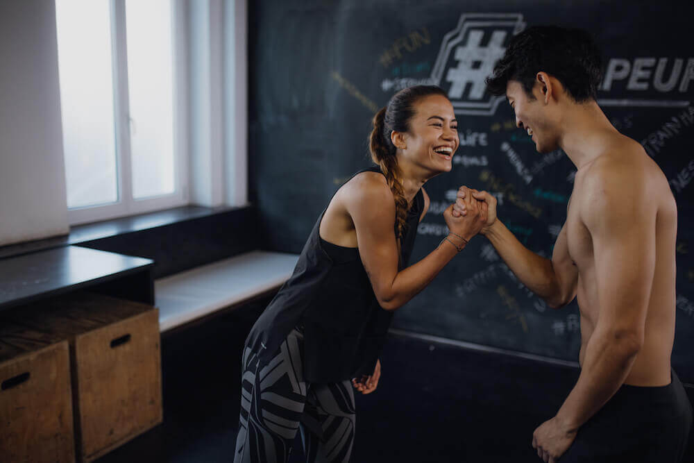 Two young people doing a workout and being happy about finishing it