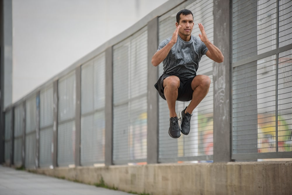 Läufer mach Squat jumps