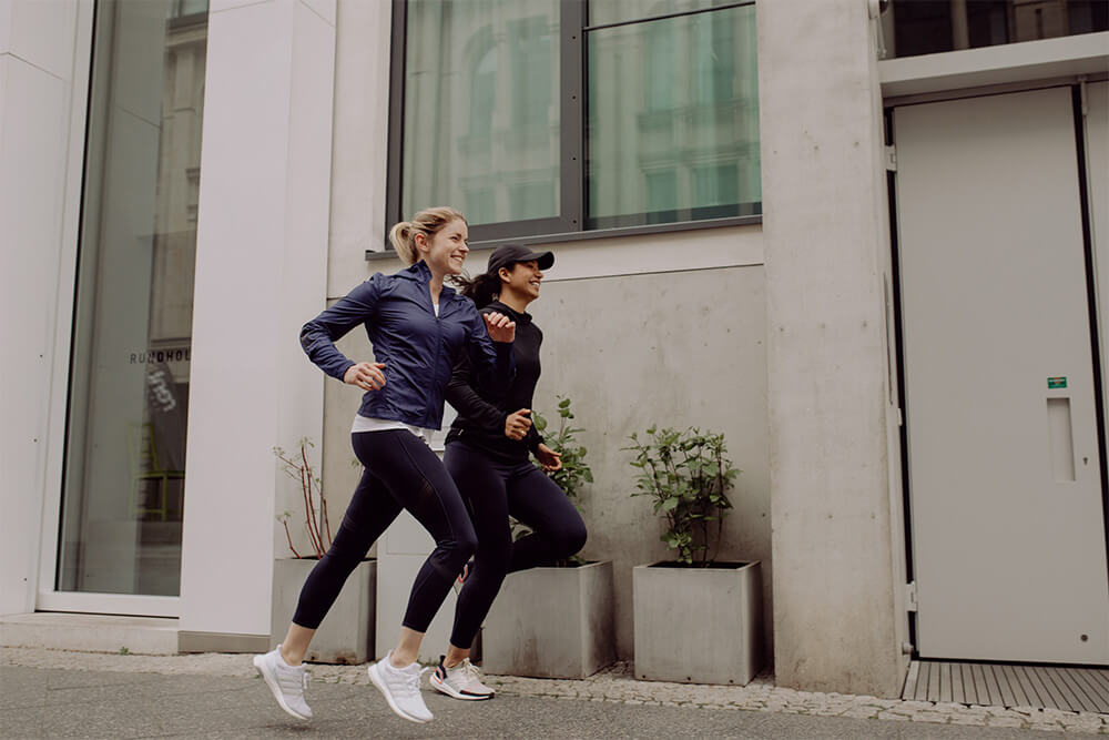 Two young women running through a city