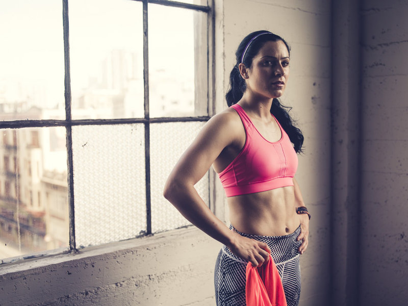 Young woman taking a break between training sets in the gym.