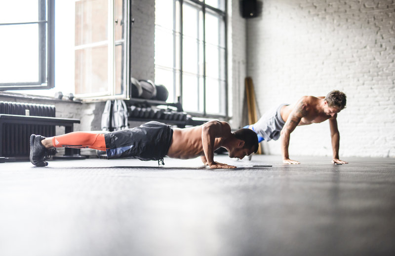Zwei Männer mit nacktem Oberkörper machen Push-ups