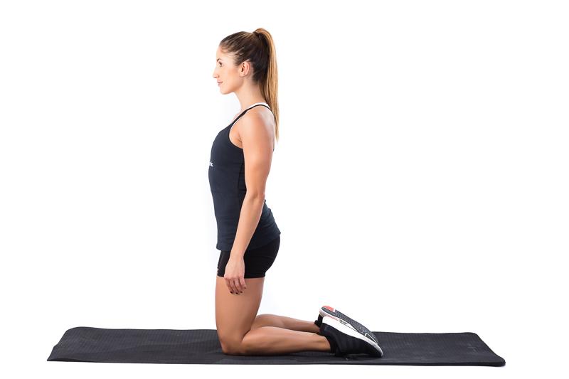 Jeune femme à genou sur un tapis