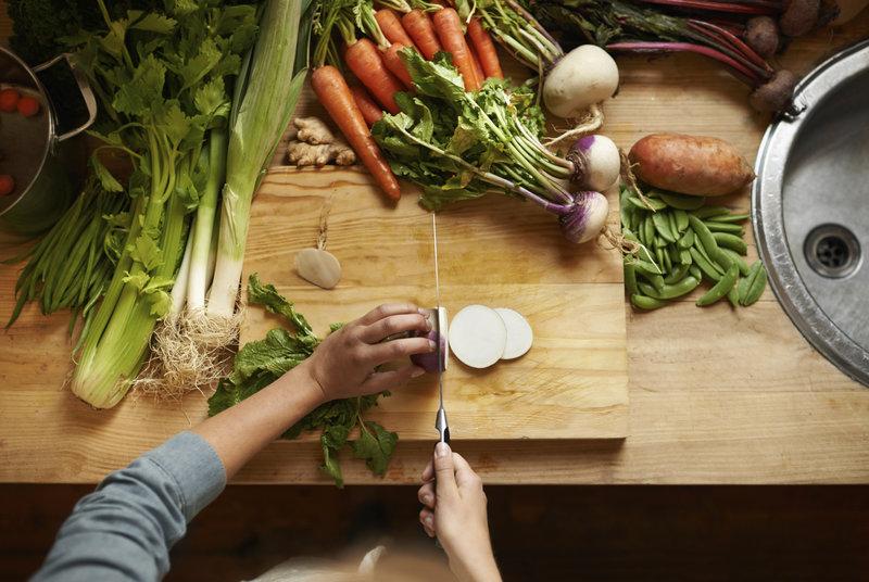 Frau schneidet Gemüse am Schneidbrett