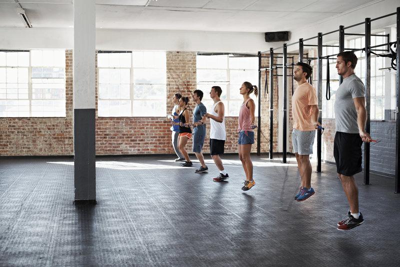 Grupo treinando junto, pulando corda em um salão