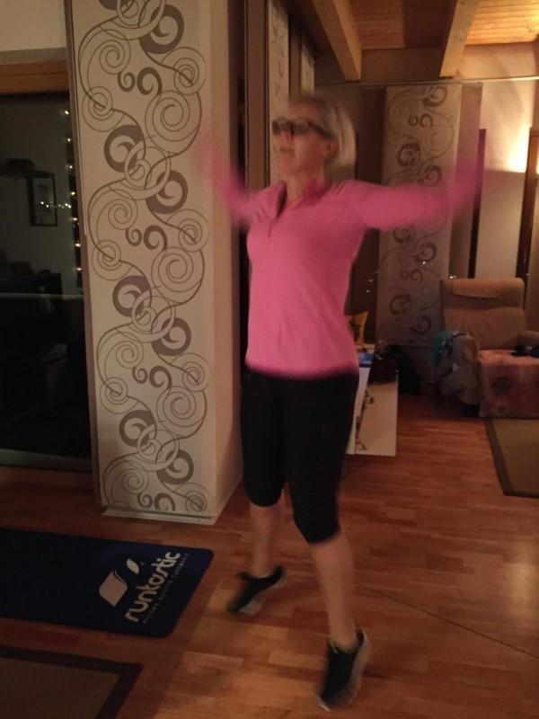 woman doing jumping jacks at home