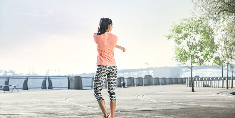 Young woman is stretching after running.