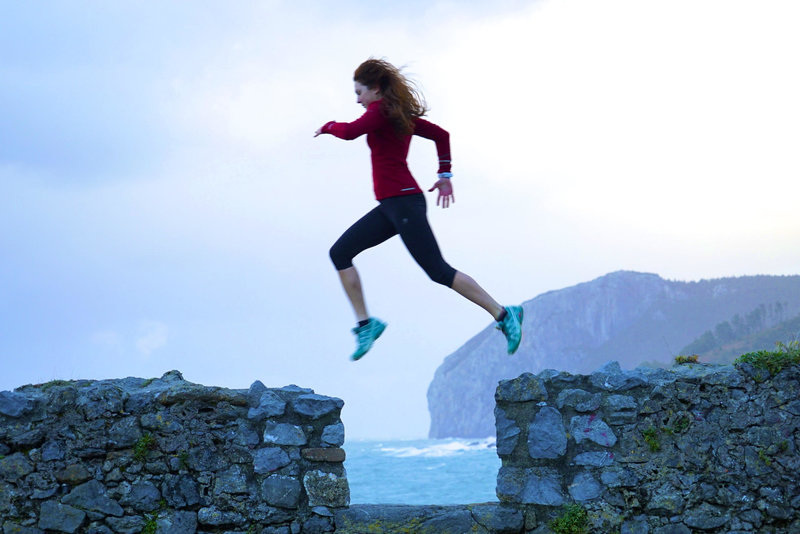 Shot of young woman jumping .