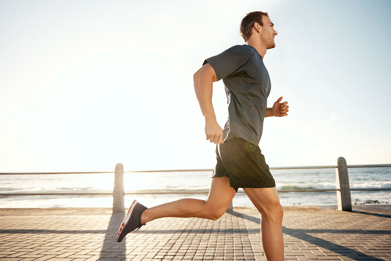 Young man running by the sea.