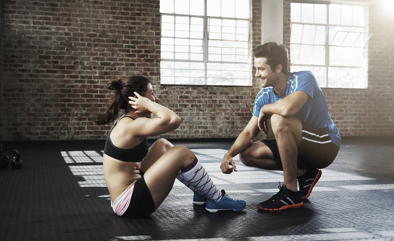A man supporting a woman who is doing sit-ups