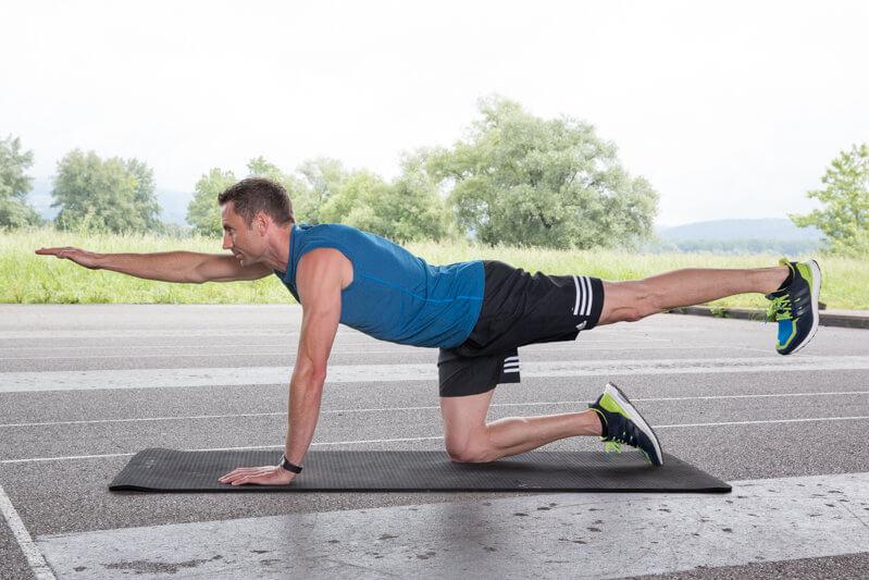 Homem fazendo levantamento de perna e braços sobre 4 apoios.