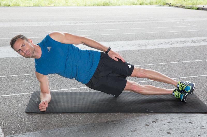 Athletischer Mann macht eine Low-side-plank mit Fußheben nach vorne und hinten.
