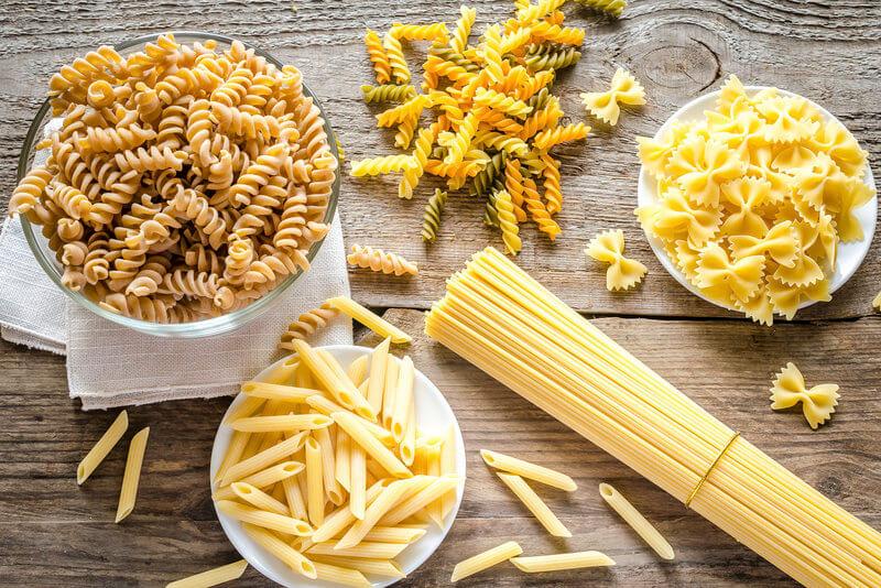 Différentes sortes de pâtes sur une table en bois.