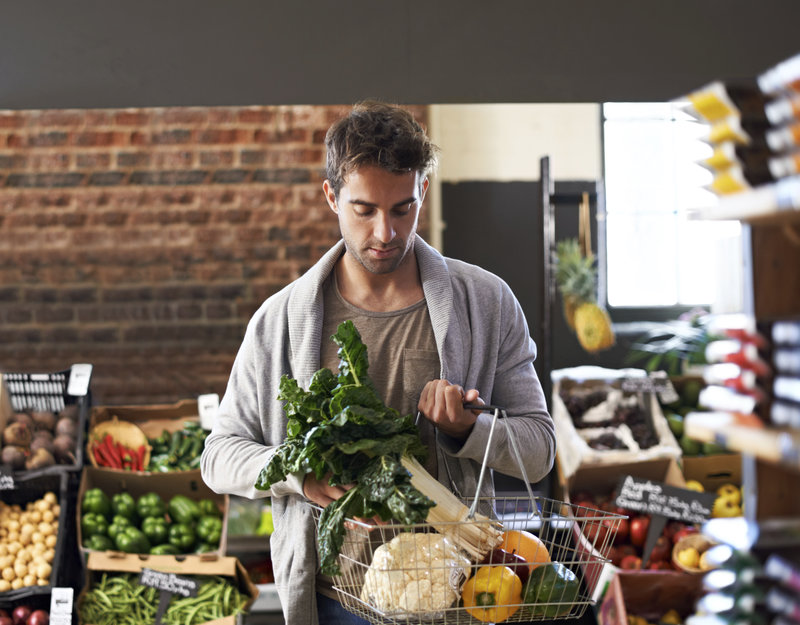 Shot of a young man walking in a grocery store with a basket full of fresh produce