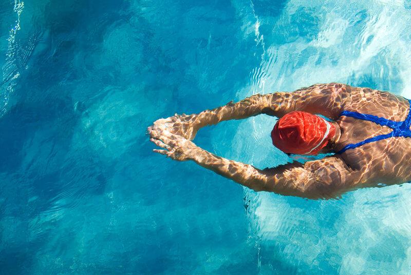Sportliche Frau beim Tauchen im Pool.