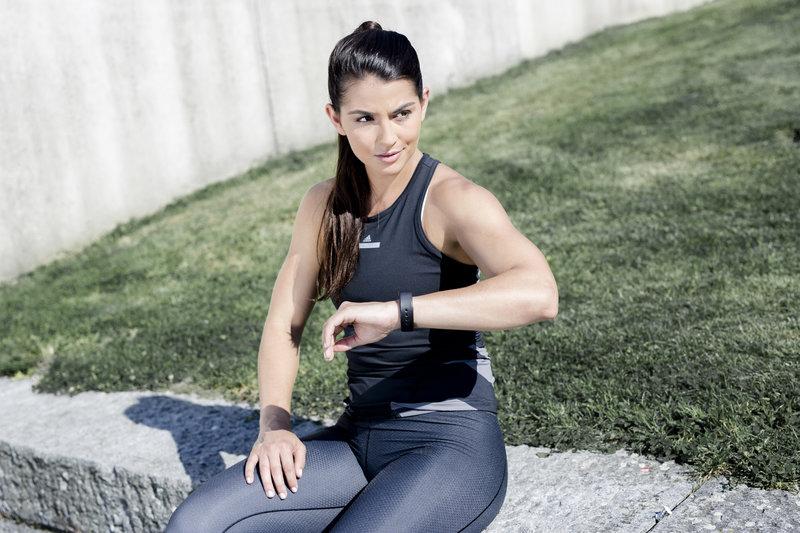 Jeune femme qui consulte son bracelet connecté aprés l'entraînement.