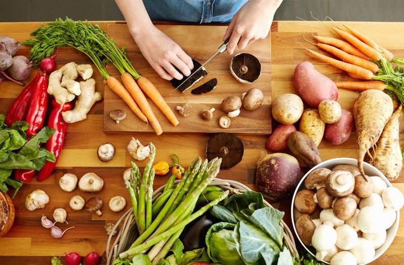 Punto de vista de alto ángulo de manos femeninas cortando hongos portobello. Varios vegetales frescos y saludables están en la mesa de madera. La mujer está cocinando la comida. Ella es cocina doméstica.