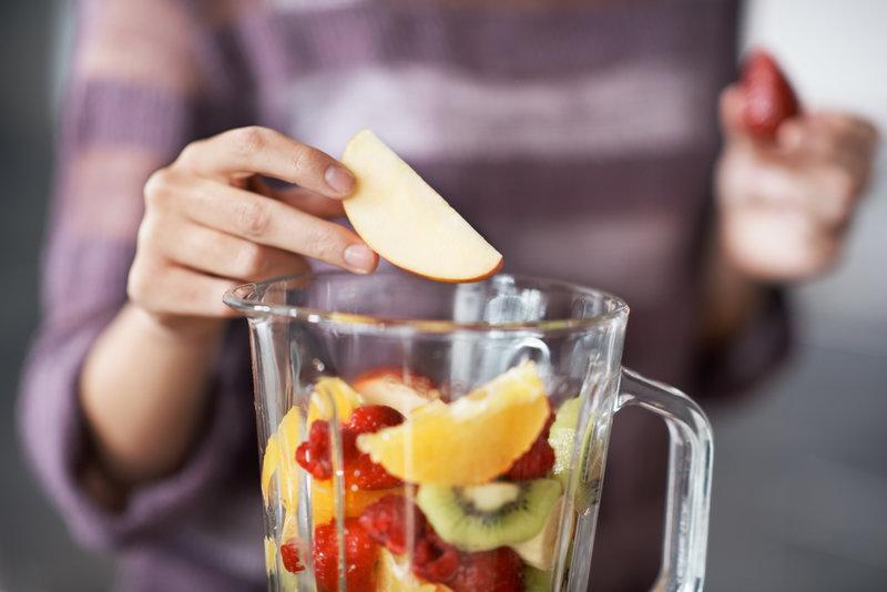 Gros plan sur des mains de femmes mettant des fruits dans un blender.
