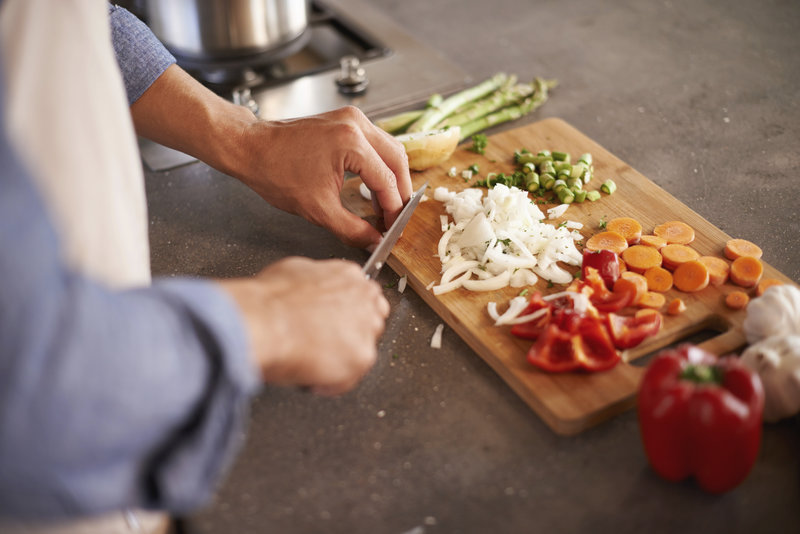 Cropped shot of a man chopping vegetables on a countertop