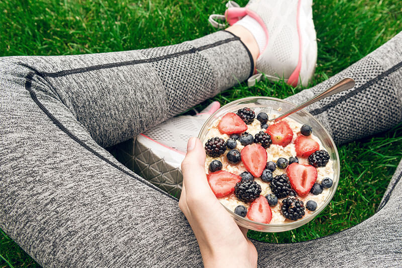Woman sitting in the gras with a bowl of muesli and fresh fruits.