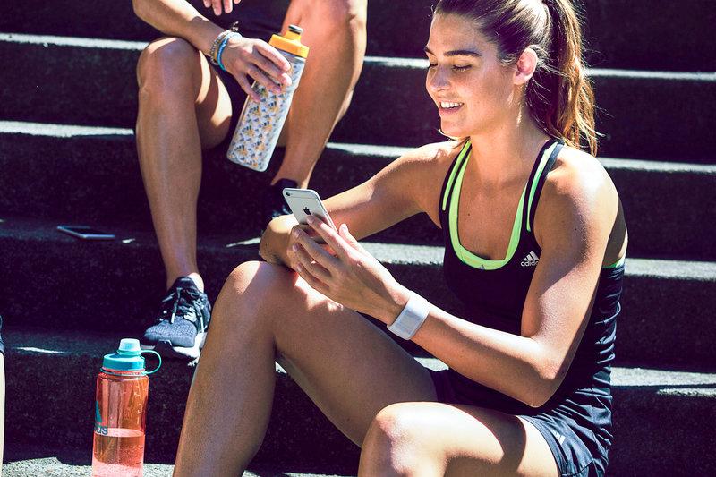 Junge Frau im Sportgewand sitzt auf einer Stiege und checkt ihr Smartphone.