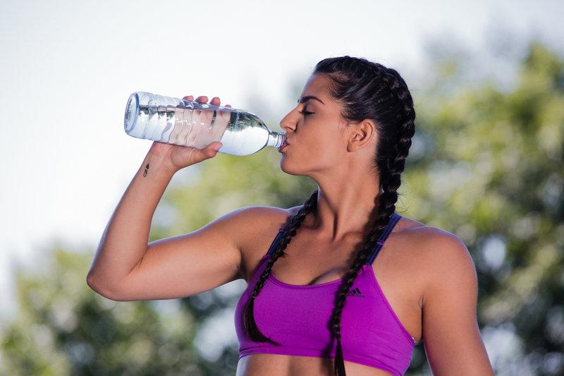 Junge Frau trinkt nach dem Training aus ihrer Wasserflasche.