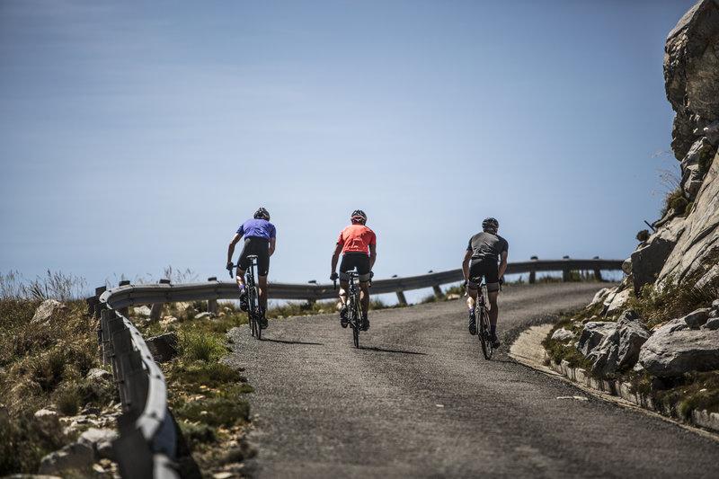 Three men are biking uphill