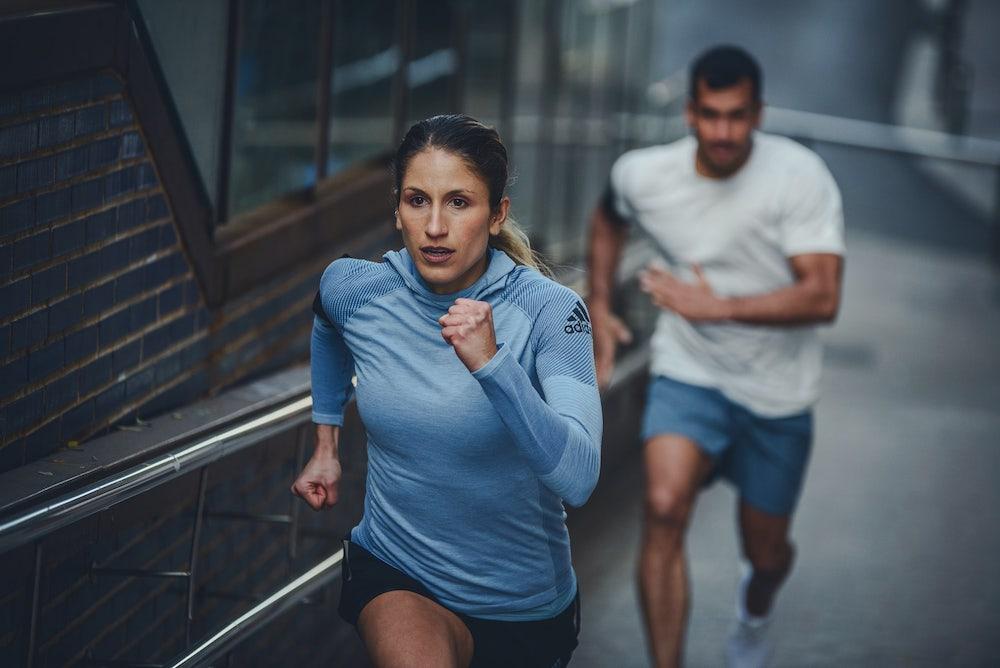 mulher e homem fazendo sprint na subida