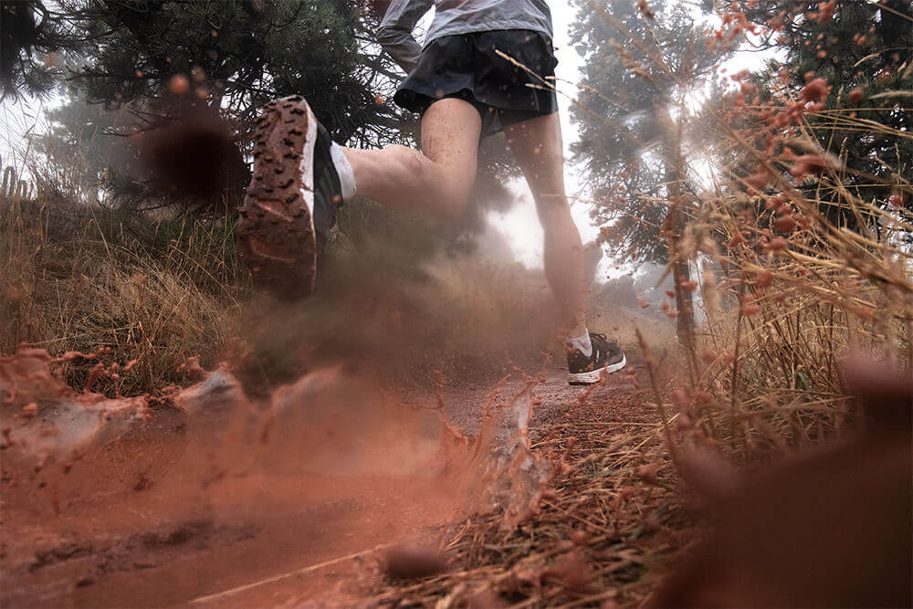 A trail runner in adidas Terrex equipment running on a trail