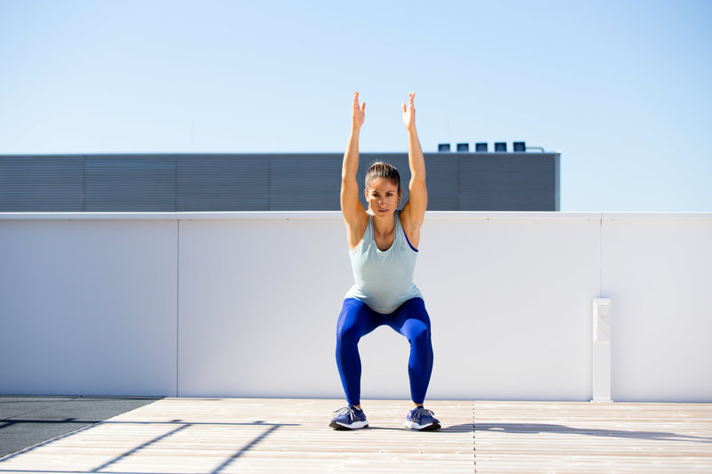 Woman is doing a squat with her feet turned out