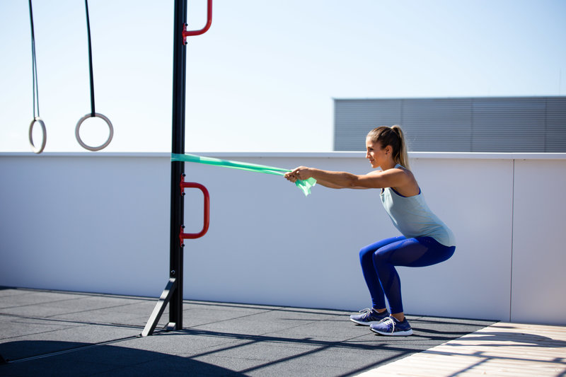Woman doing a squat to row