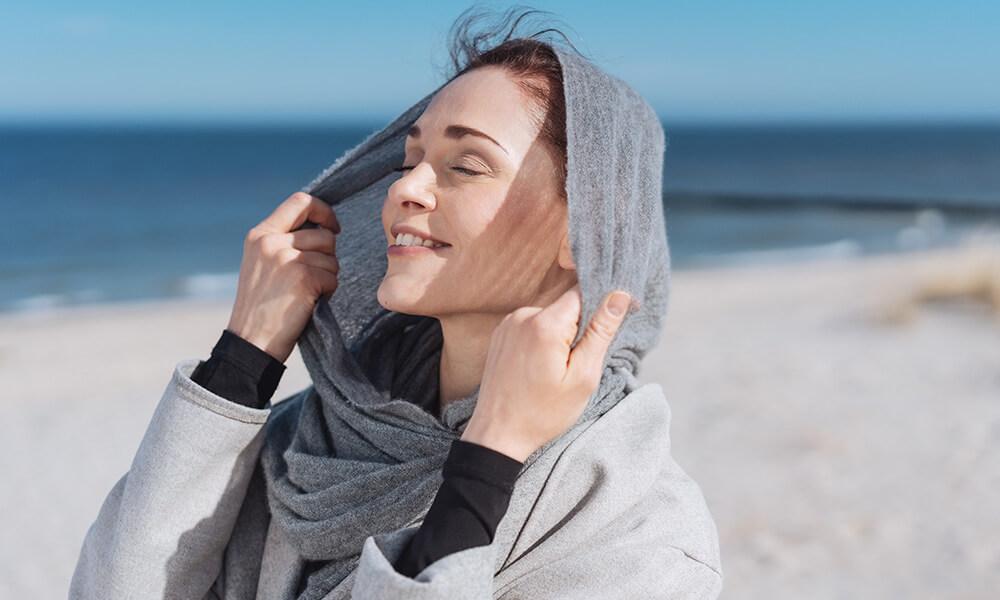 Ein Mann steht am Strand und hält ihr Gesicht in die Sonne
