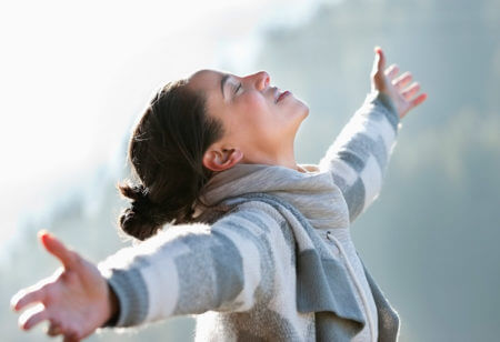 Eine Frau streckt ihre Arme aus, lacht und hält das Gesicht zur Sonne