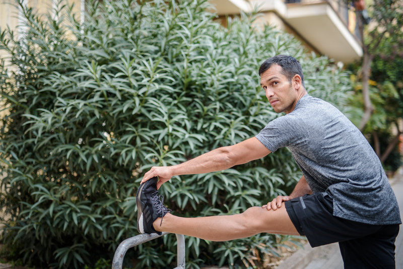 A man is stretching his leg after a run