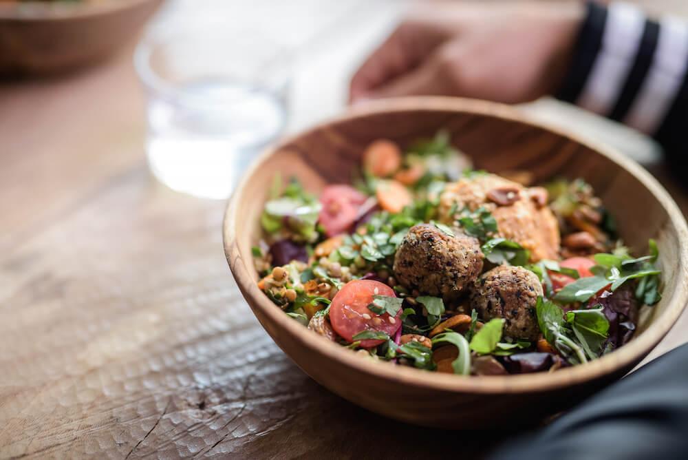 un bol avec des légumes et des falafels