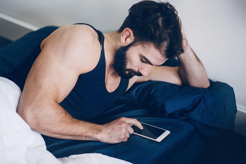 Ein Mann liegt im Bett und scrollt am Handy durch seinen Newsfeed