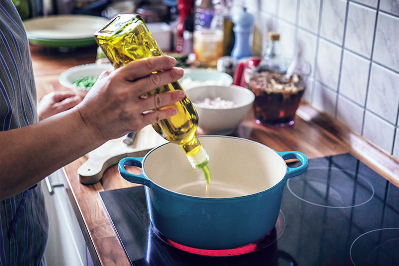 Someone pouring vegetable oil into a pan