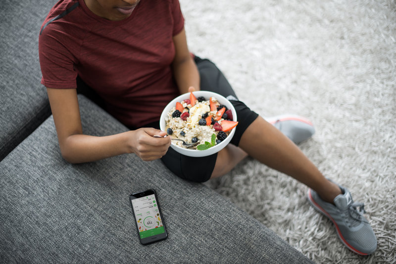 A woman eating granola with yoghurt and fruits on the couch