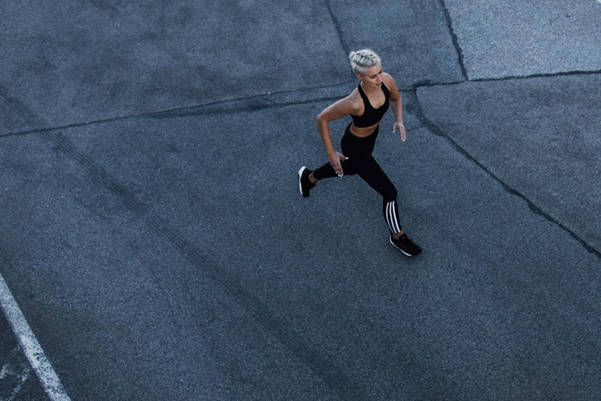 Una mujer corriendo sobre asfalto