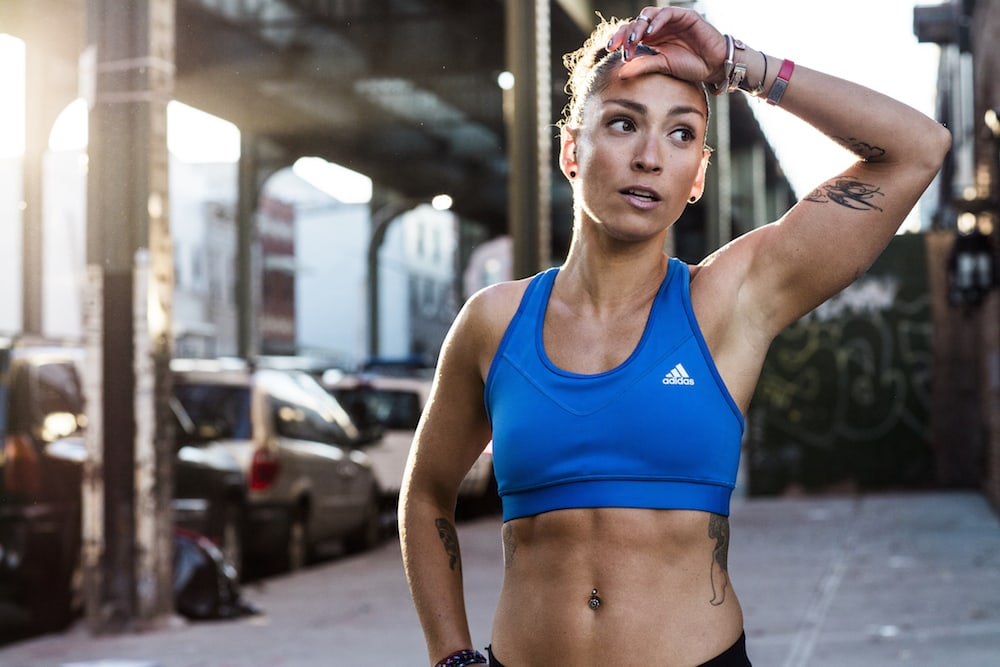 Une femme avec des vêtements de sport adidas fait une pause pendant sa course