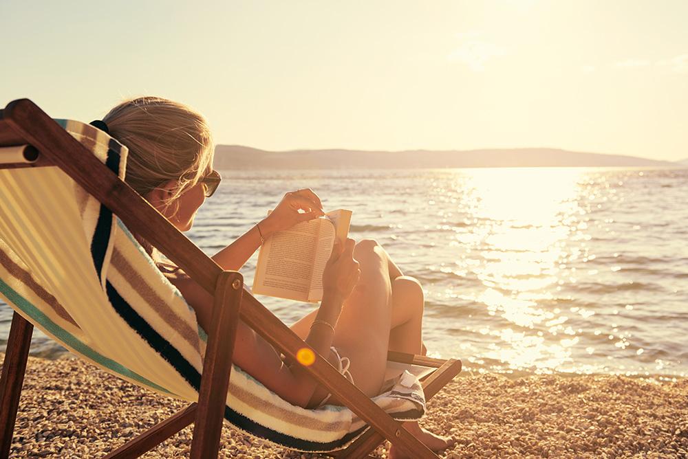 Eine junge Frau lässt sich im Liegestuhl am Strand sonnen und liest dabei ein Buch.