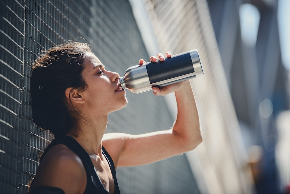 Woman drinking water after a run