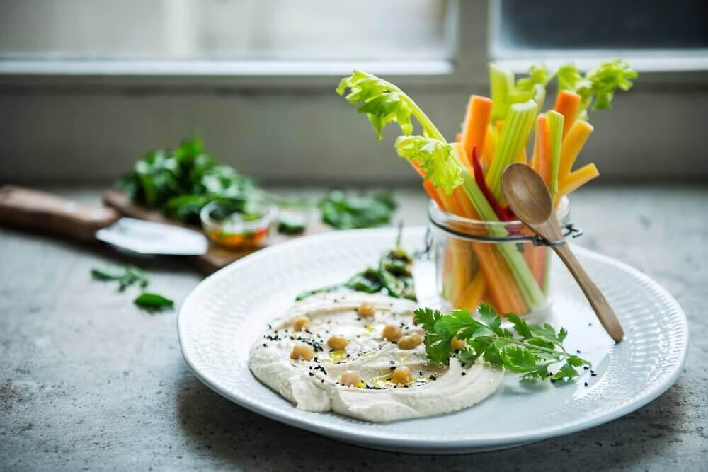 Prato contendo palitos de cenoura e de aipo e uma porção de homus