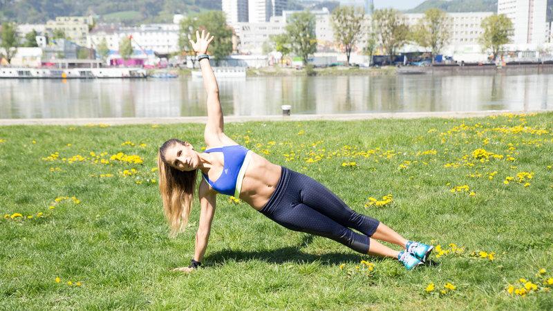 Junge Frau macht eine Push-Up Siede Plank im Freien.