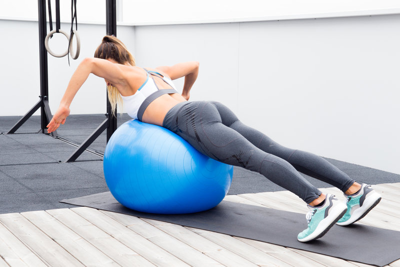 Woman is doing Prone ball wide rows with rotation